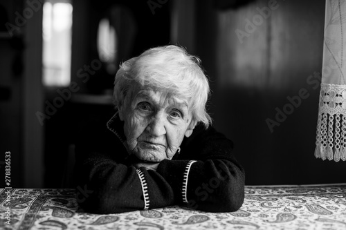 Black and white portrait of a lonely sad old woman.