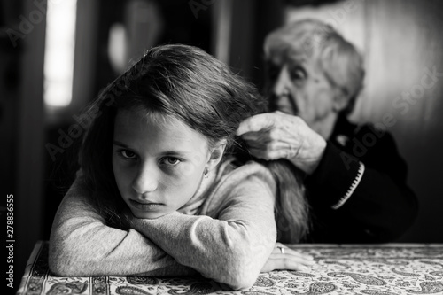 An old woman braids her great-granddaughter's hair. Black and white photography.