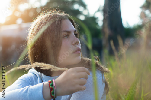 Young woman sitting in green grass in summer countryside. Photo shoot in the sunlight.