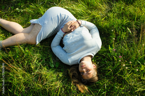 Young girl lying in green grass in the summer. Photo view from the top..