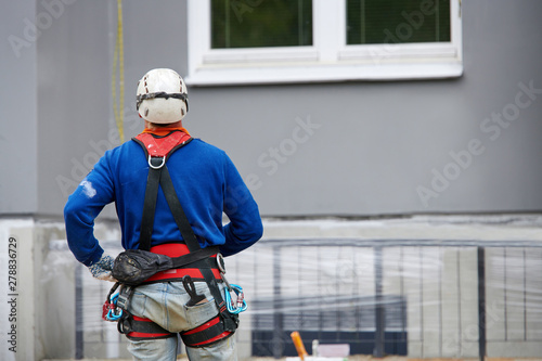 Professional industrial alpinist with rigging equipment, hardhat and safety harness from the back Wallpaper Mural