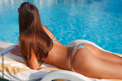 Portrait of sexy tanned slim model woman in sunglasses and colorful bikini have relax and enjoy in swimming pool. Hot summer day and bright sunny light. Luxury travel tropical resort concept