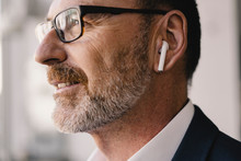 Portrait Of Mature Businessman Listening To Music With  Earbuds
