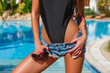 canvas print picture - Portrait of sexy tanned slim model woman in black exotic bikini, jeans denim shorts and sunglasses having relax and enjoying in swimming pool. Red gel polish manicure. Luxury tropical resort concept