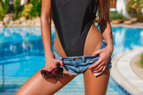 Obraz Portrait of sexy tanned slim model woman in black exotic bikini, jeans denim shorts and sunglasses having relax and enjoying in swimming pool. Red gel polish manicure. Luxury tropical resort concept - fototapety do salonu