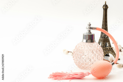 Fototapeta Pure essence perfumes, fragrance of France and romantic mood in Paris concept theme with a vintage bottle of french perfume next to the Eiffel Tower isolated on white background with copy space obraz