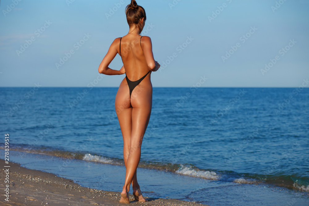Fototapeta Sexy back of a beautiful woman in black little bikini on sea background. Exotic model at the beach. Sexy buttocks, tanned skin and fit butt
