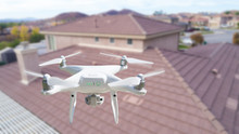 Unmanned Aircraft System (UAV) Quadcopter Drone In The Air Over House Inspecting The Roof