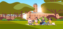 Young Teenage Students Group Sitting On Grass At Campus Yard Education Concept College Friends Relaxing And Talking In Front Of University Building Exterior Horizontal Full Length
