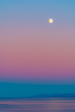 Moon With Pink Skies At Blue Hour Twilight Before Sunrise/ Following Sunset Over Ocean With Reflection In Water And Mountain Silhouette In Background. Colorful Scenic Nature And Landscape Setting.