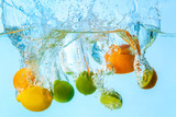 Falling of different fruits into water on light background