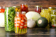Jars with different canned vegetables on wooden table