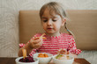Cute little girl eating assorted tasting appetizing snack at table