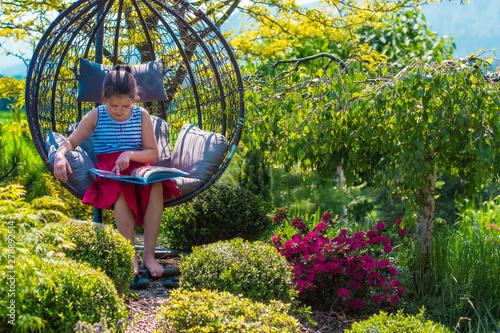Fototapeta relaksi odpoczynek z książką na ogrodzie wśród kwiatów obraz