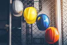 White, Yellow, Blue And Orange Helmets That Hang On The Iron Fence At The Construction Site.