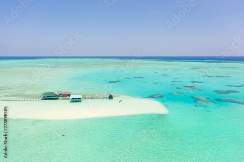Foto auf Leinwand Reef grun Bungalow and boat on the sea shallows, view from above. Seascape with coral reef, lagoon and sandbar. Onok Island Balabac, Philippines.