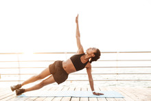 Image Of Beautiful Woman Doing Exercises On Finess Mat While Working Out By Seaside In Morning