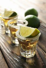 Tequila Shots With Salt And Lime Slices On Wood Table, Closeup