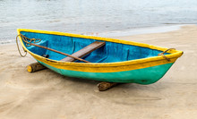 Beautiful Photo Of Beached Fishing Canoe, The Canoe Is Painted Colorful In Traditional Asian Manner. It Is Idle In Off Season Parked On Wooden Logs, Due To Rough Weather Forecast Of Cyclone. - Image