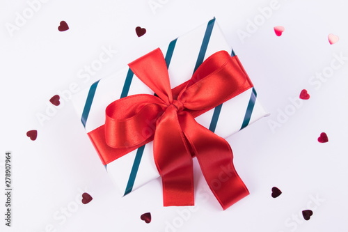 In de dag Hert Gift box with green lines and red satin bow on a white background with glitter hearts. Festive concept. Isolated.