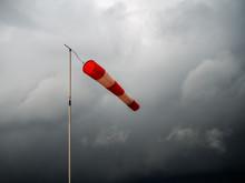 Red Windsock On Black Stormy Sky. Bad Weather, Meterological Wind Indicator.