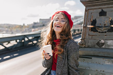Interested Caucasian Girl In Vintage Outfit Drinking Coffee During Trip Around Europe. Outdoor Photo Of Cute French Lady In Red Beret Enjoying Tea While Posing In Sunny Day With Sincere Laugh.