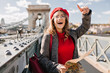 Leinwanddruck Bild - Enchanting female tourist exploring France with map. Outdoor portrait of happy brunette woman in red beret and glasses searching Paris attractions.