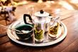 Marokkanischer Minztee in Gläsern serviert auf einem silbernen Tablett mit einer Teekanne und Schale