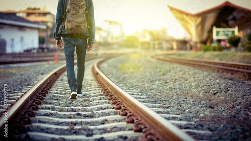 Papiers peints Voies ferrées Man walk away on railroad with warm light.Selective focus.Traveler man on railroad.
