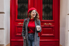 Glad White Female Model In Long Gray Jacket Looking Away With Smile Standing Near Red Door. Outdoor Photo Of Beautiful Caucasian Woman In Sweater Drinks Coffee In Front Of Cafe And Laughing.