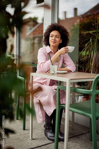 Attractive mixed race woman sitting in cafe and enjoying her coffee Canvas