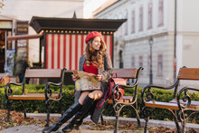 Winsome Caucasian Woman In Knee High Shoes Sitting In Park With City Map. Romantic Young Lady With Long Hairstyle Waiting Someone On Bench And Smiling.