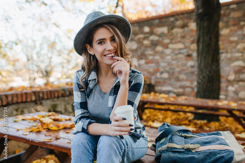 Fototapety, obrazy: Interested young lady with cup of coffee posing in park in october day. Adorable woman in hat with black manicure spending time in yard in autumn morning.
