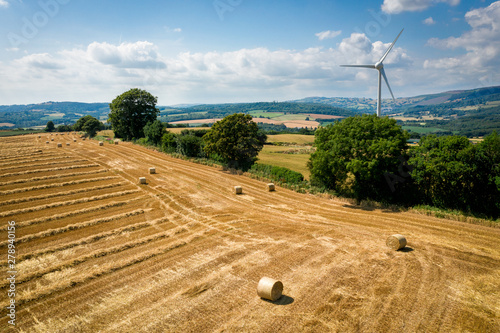 Fotografia  Aerial view of Straw bales with a wind turbine on farmland in Wales UK