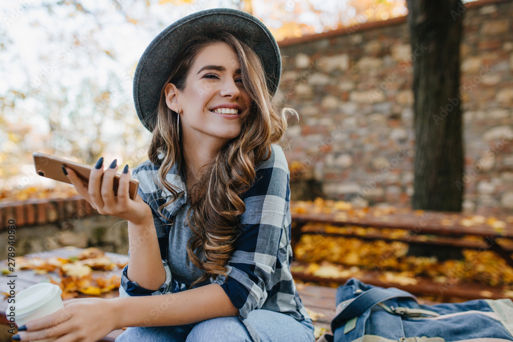 Fototapeta Pretty laughing girl with smartphone has a good time in autumn weekend. Outdoor portrait of lovable trendy lady with brown hair wears hat in october day.