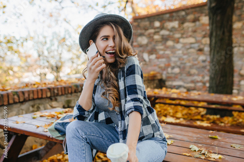 Fototapety, obrazy: Sensual curly woman in hat expressing funny emotions during photoshoot in autumn yard. Glad cute girl with light-brown hair looking away with smile, talking on phone.