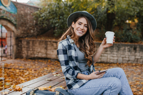 Fototapety, obrazy: Playful girl in blue jeans sitting on wooden table and enjoying good autumn day. Pretty caucasian lady with light-brown hair drinks latte in yard in october morning.