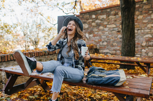 Photo  Fascinating young woman wears jeans laughing while talking on phone in park with yellow trees