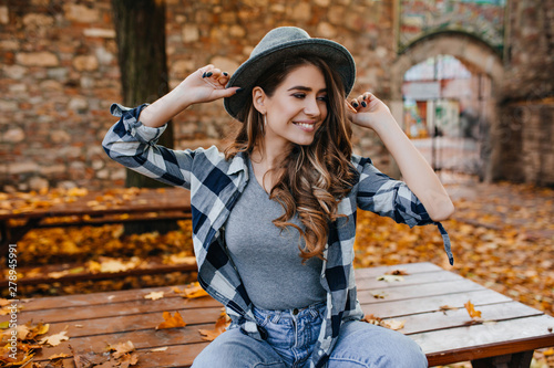 Magnificent pale girl in trendy hat sitting on table in park and smiling Canvas Print