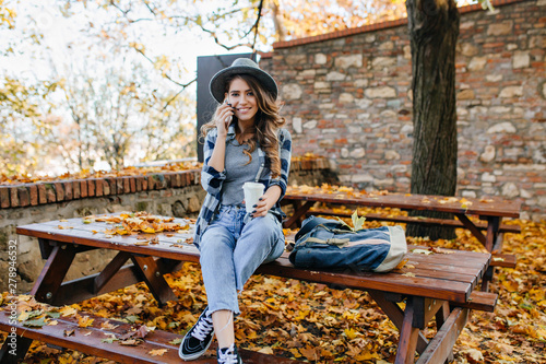 Photo  Gorgeous slim lady wears short jeans sitting on table with legs crossed in autumn day
