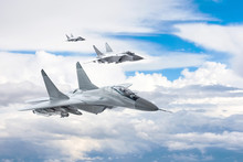 Three Combat Fighter Jet On A Military Mission With Weapons - Rockets, Bombs, Weapons On Wings Flies High In The Sky Above The Clouds.