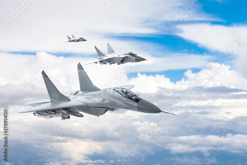Three combat fighter jet on a military mission with weapons - rockets, bombs, weapons on wings flies high in the sky above the clouds Fototapeta