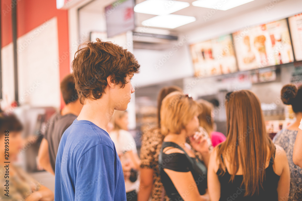 Fototapety, obrazy: young teenager standing in a queue to receive the fastfood package