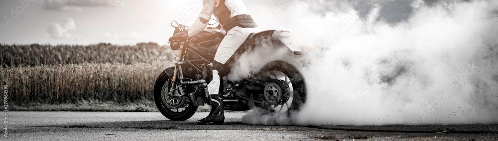 Fototapeta wilder Motorradfahrer lässt die Reifen bei einem Burnout durchdrehen und macht einen Donut