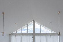 Interior View Of Triangle Shape Window With White Curtain And Cloud Sky.