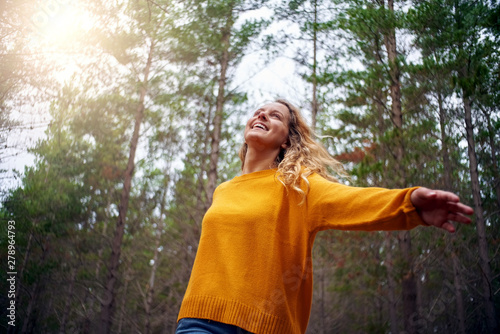 Obraz Beautiful happy blonde young woman dancing in forest - fototapety do salonu