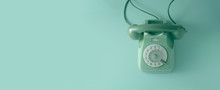 A Green Vintage Dial Telephone With Green Background.
