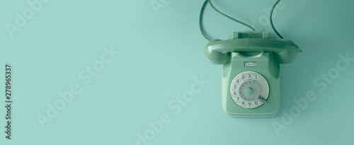 Photo A green vintage dial telephone with green background.