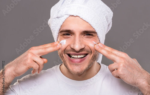 Poster de jardin Route Millennial guy with towel on his head, applying cream on face