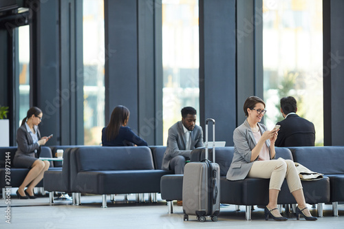 Fotografía  Business people wasting time in airport: cheerful attractive woman sitting on so